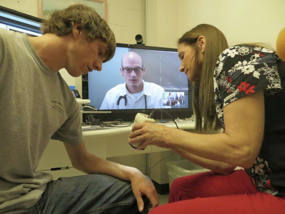 Canyon High School Nurse Regina Smith uses a scope to let Dr. Robert Morin (on television screen) remotely examine a cut on a student's arm. Photo: Zeke MacCormack / San Antonio Express-News