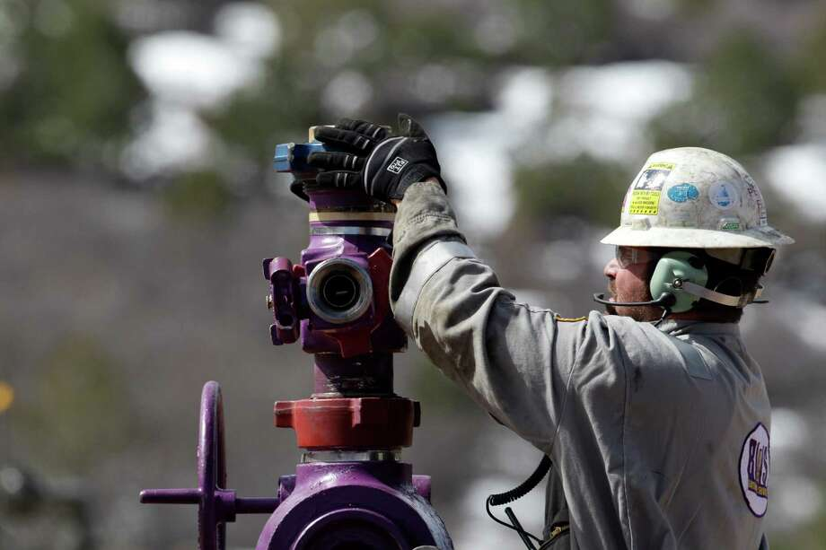 A worker switches well heads at a fracturing site in western Colorado. The spread of fracturing to low-rainfall areas could trigger competition for water, a co-author of a water study says. Photo: Brennan Linsley, STF / AP
