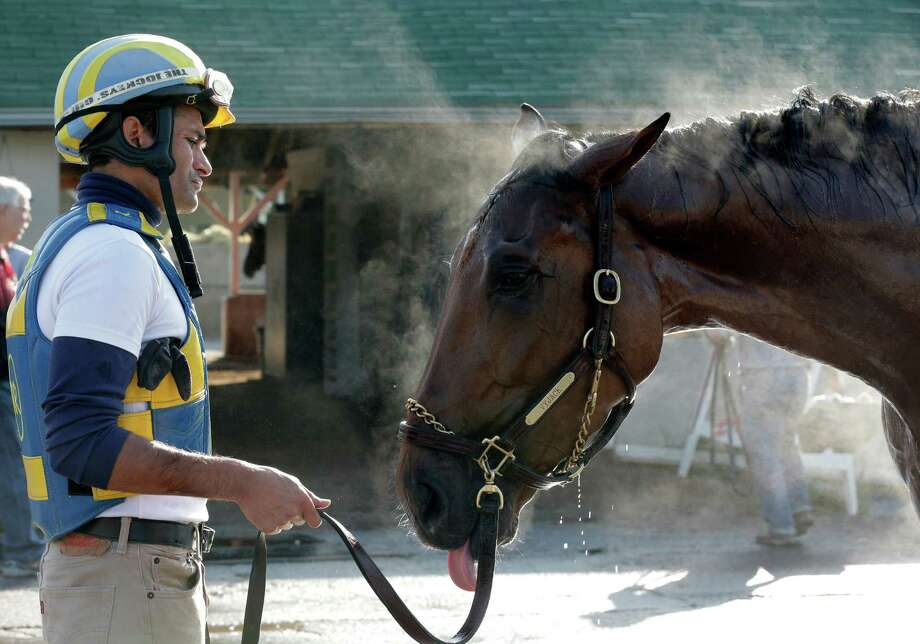 Trainer Rudy Rodriguez watches Kentucky Derby hopeful Vyjack get a bath after a workout at Churchill Downs Tuesday, April 30, 2013, in Louisville, Ky. (AP Photo/Charlie Riedel) Photo: Charlie Riedel, STF / AP