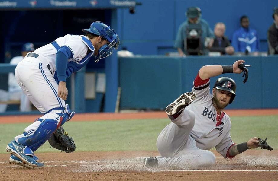 Boston Red Sox's Mike Napoli, right, slides safely into home plate as Toronto Blue Jays catcher J.P. Arencibia, left, is late on the tag during the second inning of their baseball game, Thursday, May 2, 2013, in Toronto. (AP Photo/The Canadian Press, Nathan Denette) Photo: Nathan Denette