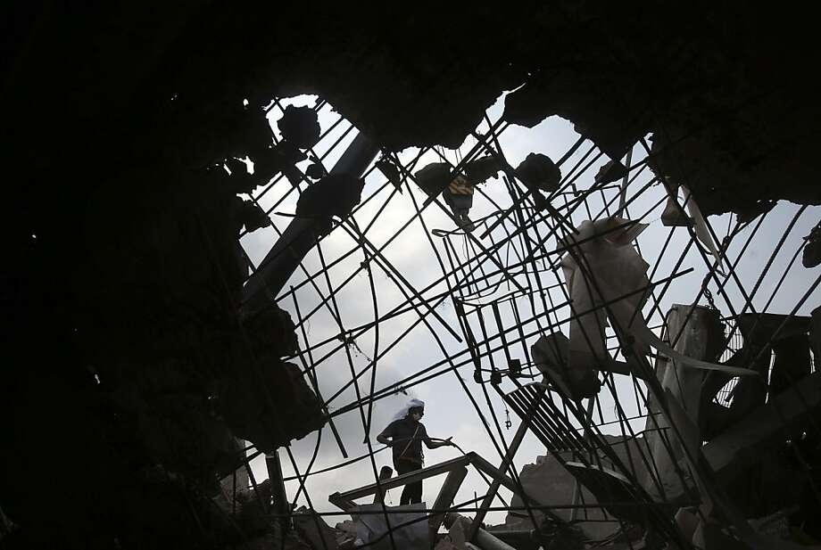A worker is seen through a broken cement wall as he toils in the collapsed garment factory building in search for bodies on Thursday, May 2, 2013, in Savar, near Dhaka, Bangladesh. Rescuers found more bodies in the concrete debris of the collapsed garment factory building Thursday and authorities say it may take another five days to clear the rubble. In addition to the 430 confirmed dead, police report another 149 people are still missing in what has become the worst disaster for Bangladesh's $20 billion-a-year garment industry that supplies global retailers.  Photo: Wong Maye-E, Associated Press