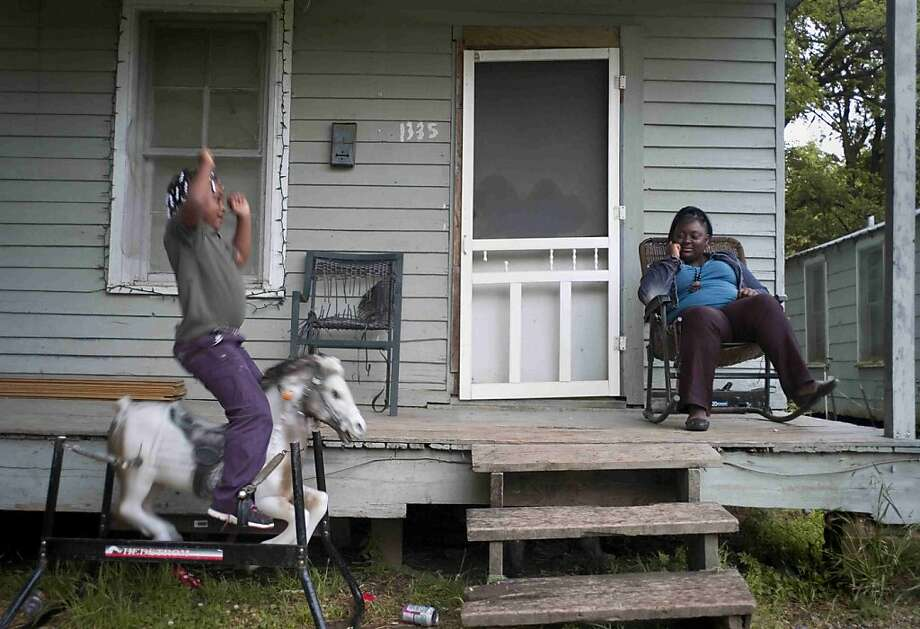 Ma'Keria Lyons, 6, left, rides a toy horse as her mother, Michelle Thomas, watches from their porch on East Avenue Wednesday, May 1, 2013 in Vicksburg, Miss..  Photo: Eli Baylis, Associated Press