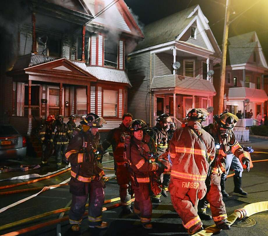 Schenectady firefighters carry a fire victim to an awaiting ambulance from a house fire at 428 Hulett Street Thursday, May 2, 2013. The fire killed four people, a father and his three children, and injured a fourth child, authorities said. It was the third fire of the night in the city of about 66,000 people and struck shortly after firefighters fought another blaze about a half-mile away. Photo: Peter R. Barber, Associated Press