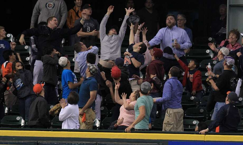 Fans in the Crawford Box reach for a home run ball hit by Astros first baseman Carlos Pena. Photo: Karen Warren, Houston Chronicle