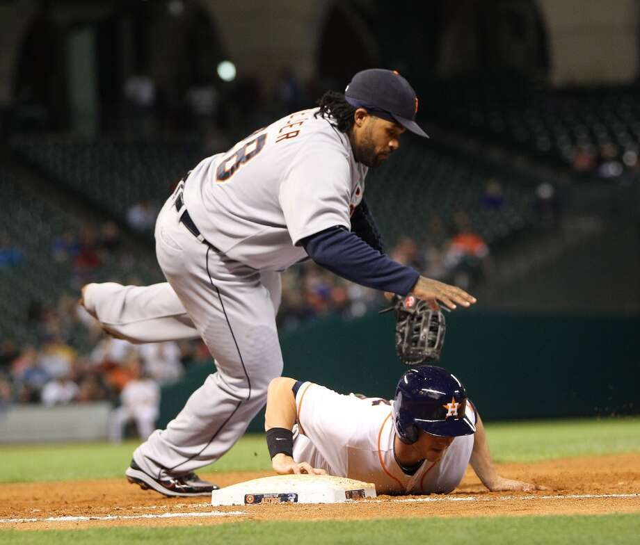 Astros center fielder Robbie Grossman dives back to first base as Tigers first baseman Prince Fielder tries to field the throw from the pitcher.