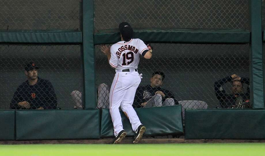 Astros center fielder Robbie Grossman crashes into the fence to catch a fly out by Tigers designated hitter Victor Martinez.