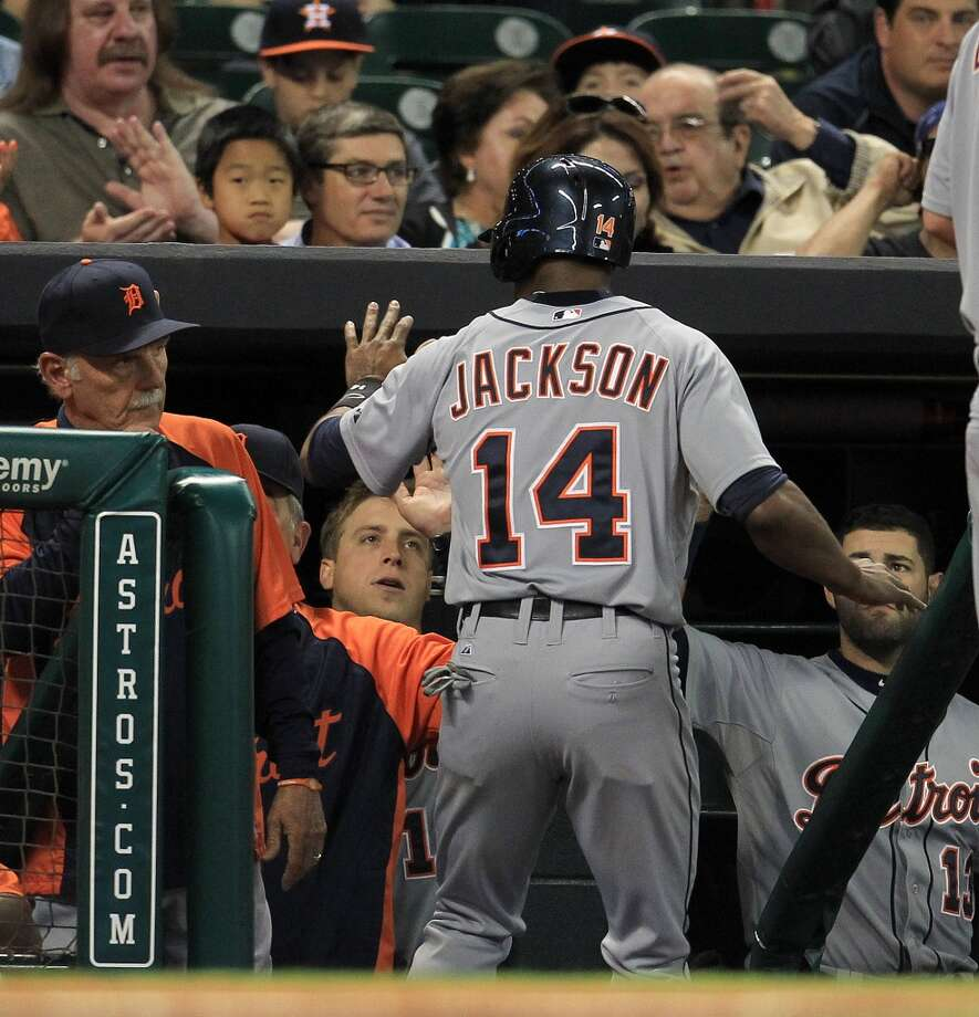 Tigers center fielder Austin Jackson celebrates with teammates after scoring a run.