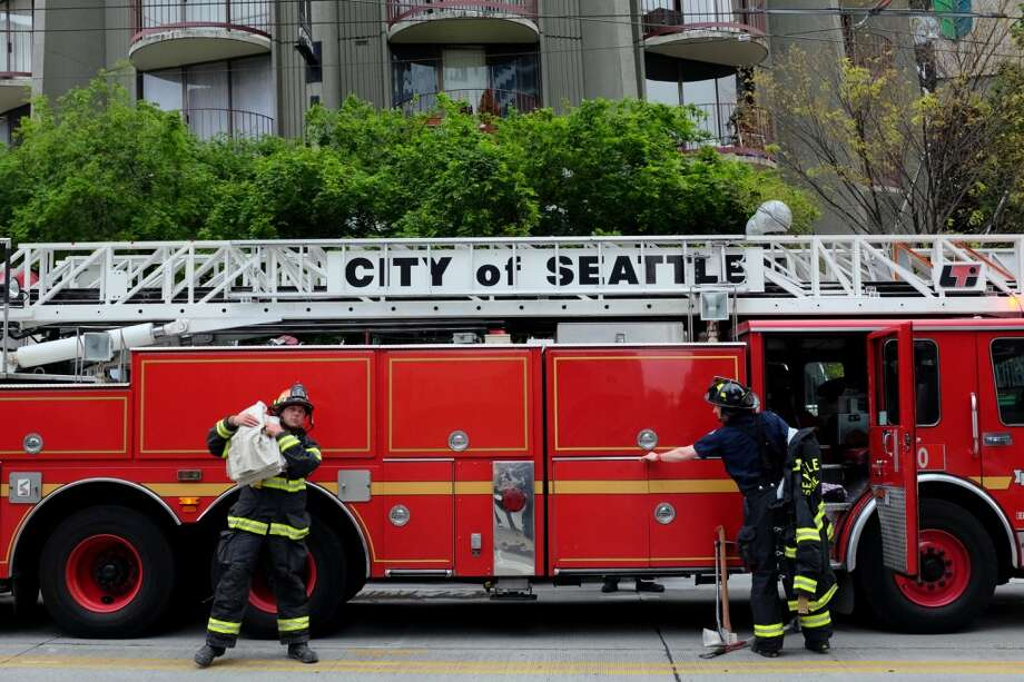 Firefighters respond to the scene of a trash chute fire that left a tower at 8th Avenue and Pine Street saturated with smoke on all floors Thursday, May 2, 2013, in Seattle. The fire was successfully put out with no injuries.