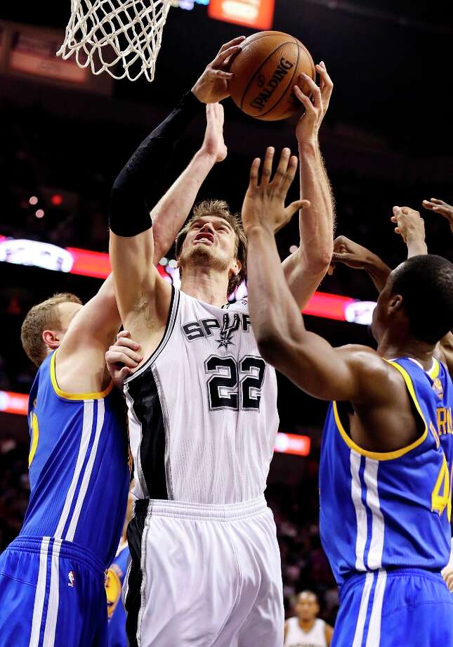 The Spurs' Tiago Splitter drives to the basket between Golden State Warriors' David Lee (left) and  Golden State Warriors' Harrison Barnes during first half action Friday Jan. 18, 2013 at the AT&T Center. Photo: Edward A. Ornelas, San Antonio Express-News / © 2012 San Antonio Express-News
