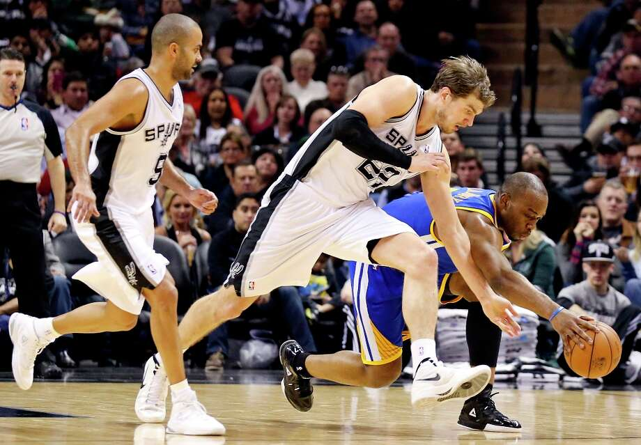 The Spurs' Tiago Splitter and Golden State Warriors' Carl Landry grab for a loose during second half action as San Antonio Spurs' Tony Parker looks on Friday Jan. 18, 2013 at the AT&T Center. The Spurs won 95-88. Photo: Edward A. Ornelas, San Antonio Express-News / © 2012 San Antonio Express-News