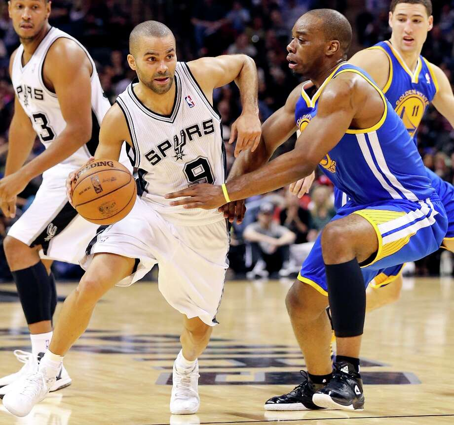 San Antonio Spurs' Tony Parker looks for room around Golden State Warriors' Carl Landry during second half action Friday Jan. 18, 2013 at the AT&T Center. The Spurs won 95-88. Photo: Edward A. Ornelas, San Antonio Express-News / © 2012 San Antonio Express-News