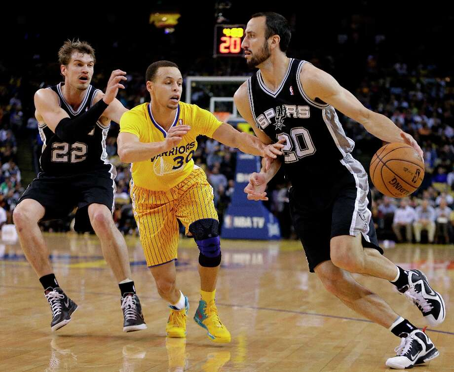San Antonio Spurs' Manu Ginobili, right, drives the ball against Golden State Warriors' Stephen Curry (30) during the first half of an NBA basketball game Friday, Feb. 22, 2013, in Oakland, Calif. At left is Spurs' Tiago Splitter (22). (AP Photo/Ben Margot) Photo: Ben Margot, Associated Press / AP