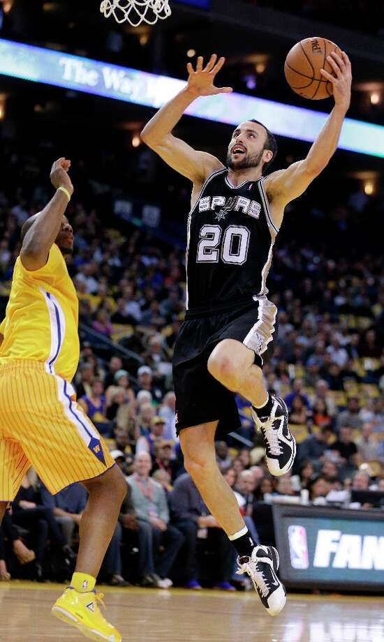 The Spurs' Manu Ginobli (20) goes to the basket next to the Warriors' Carl Landry during the first half Friday, Feb. 22, 2013, in Oakland, Calif. Photo: Ben Margot, Associated Press / AP