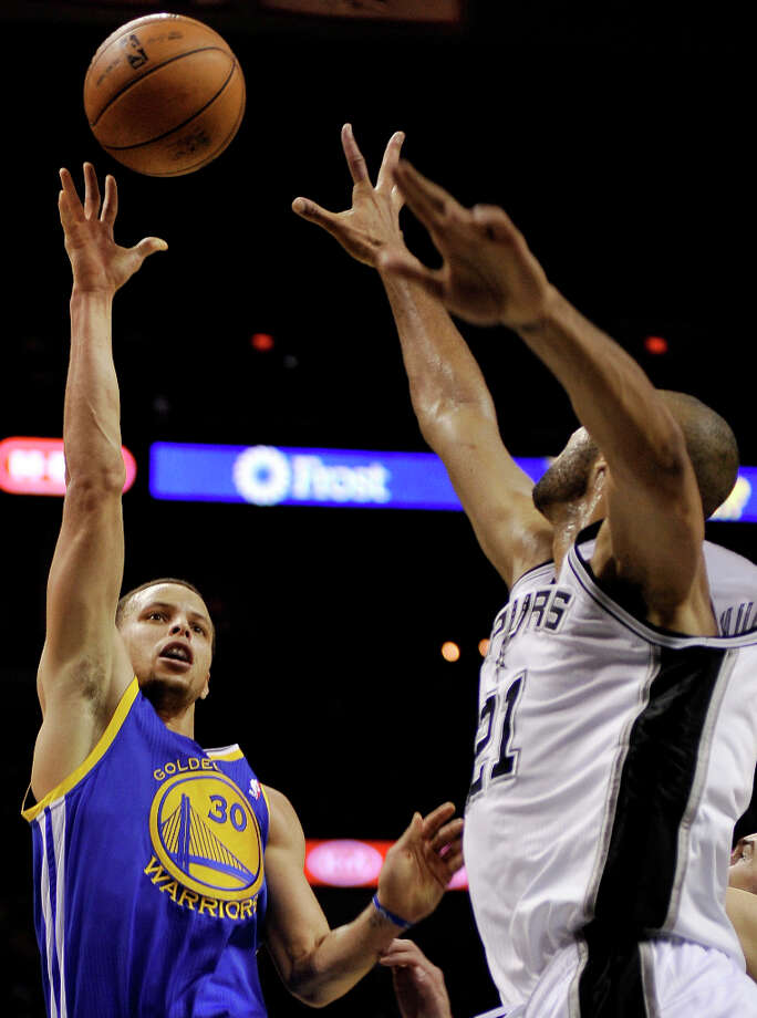 Golden State Warriors' Stephen Curry, left, shoots over San Antonio Spurs' Tim Duncan during the second half of an NBA basketball game, Wednesday, March 20, 2013, in San Antonio. San Antonio won 104-93. Photo: Darren Abate, Associated Press / FR115 AP