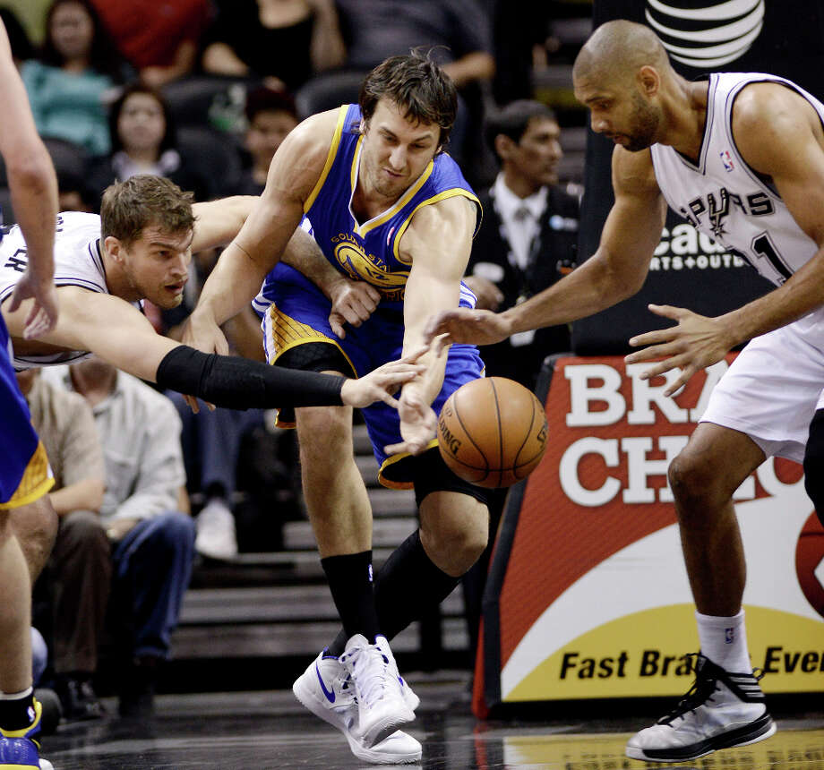 Golden State Warriors' Andrew Bogut, center, chases a loose ball against San Antonio Spurs' Tim Duncan, right, and Tiago Splitter, of Brazil, during the first half of an NBA basketball game, Wednesday, March 20, 2013, in San Antonio. San Antonio won 104-93. Photo: Darren Abate, Associated Press / FR115 AP