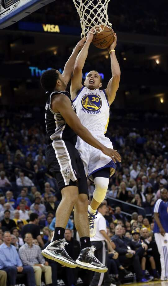 Golden State Warriors' Stephen Curry (30) scores next to the Spurs' Patty Mills during the second half in Oakland, Calif., Monday, April 15, 2013. Golden State won 116-106.