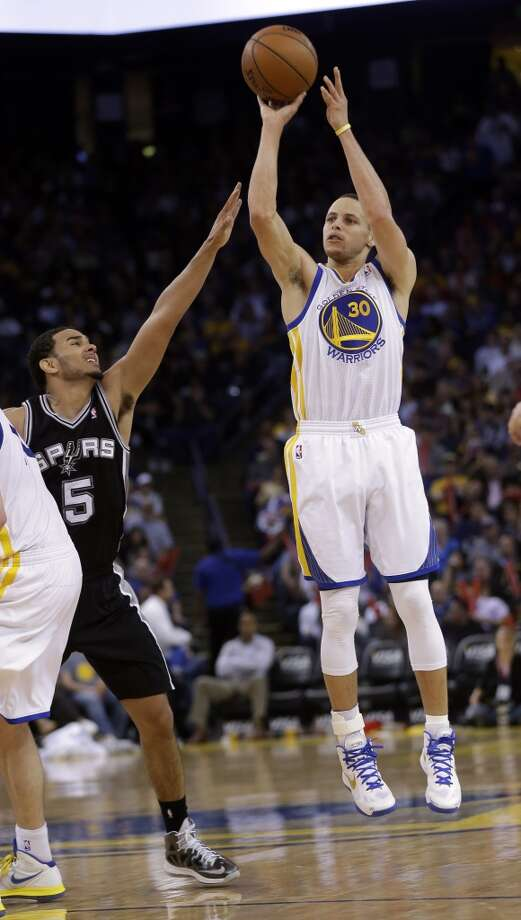 Golden State Warriors' Stephen Curry (30) makes a 3-point basket next to the Spurs' Cory Joseph (5) during the second half in Oakland, Calif., Monday, April 15, 2013. Golden State won 116-106.