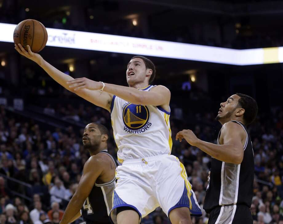 Golden State Warriors' Klay Thompson (11) scores against the San Antonio Spurs during the second half of an NBA basketball game in Oakland, Calif., Monday, April 15, 2013. Golden State won 116-106. (AP Photo/Marcio Jose Sanchez)