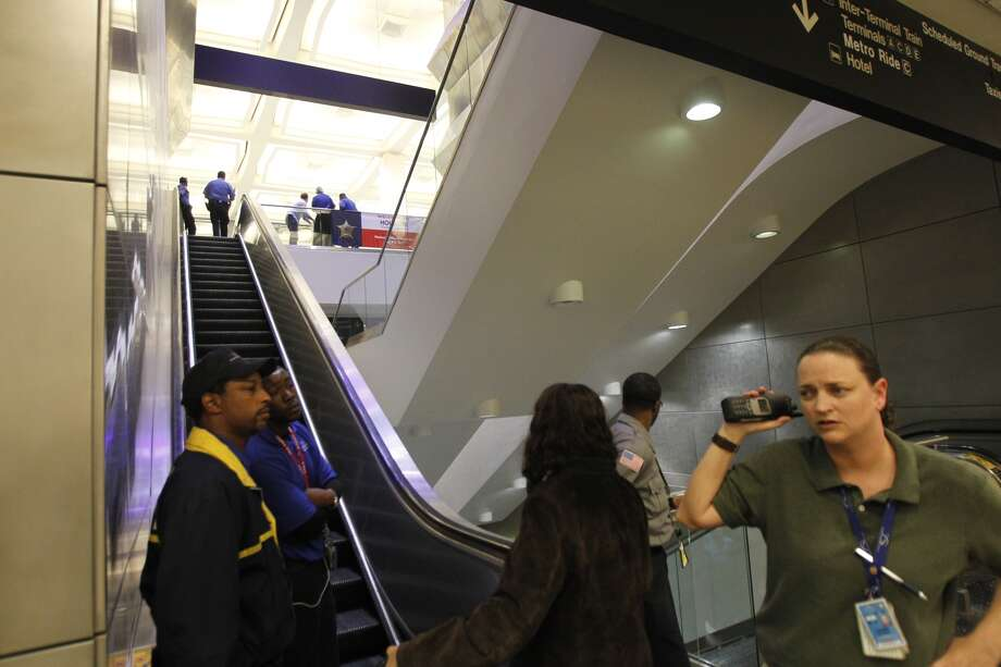 Security stands at the bottom of the escalators as police investigate a shooting in Terminal B at Bush Intercontinental Airport in Houston, Thursday, May 2, 2013. 