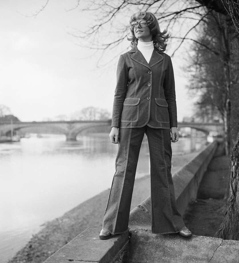 27th February 1974:  A woman stands confidently on the banks of a river, sporting a flared denim suit over a white polo-neck jumper. Photo: Chaloner Woods, Getty Images / Hulton Archive