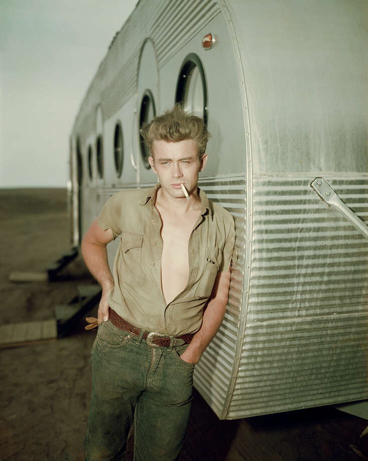 1955:  American actor James Dean (1931 - 1955) leaning against a dressing room trailer with his shirt open to the waist while smoking a cigarette on the set of director George Stevens's film, 'Giant,' in which he starred. Photo: Hulton Archive, Getty Images / Archive Photos
