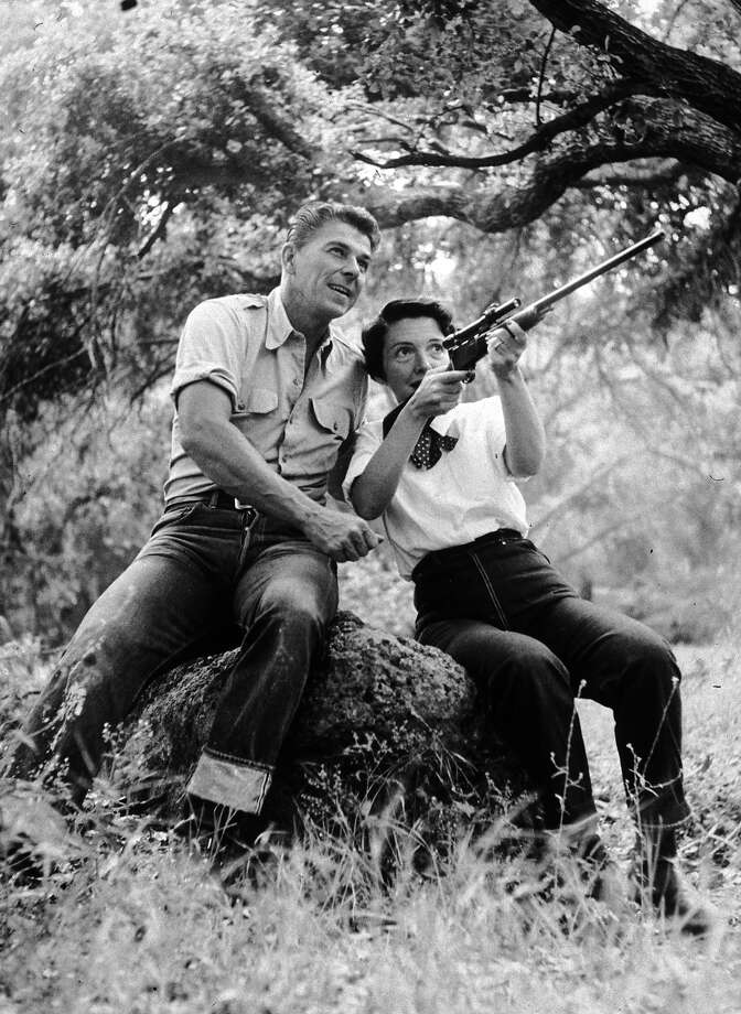 American actor Ronald Reagan watches as his wife, Nancy, aims a rifle while they sit on a large rock outdoors at their ranch in Malibu, California. Both wear jeans and their shirt sleeves rolled up. Photo: Murray Garrett, Getty Images / Archive Photos