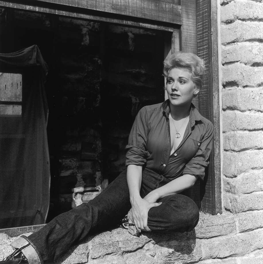 Portrait of American actor Kim Novak sitting in the large open window of a stone house, California. Novak is wearing a low-cut work shirt, jeans and cowboy boots. Photo: Murray Garrett, Getty Images / Archive Photos