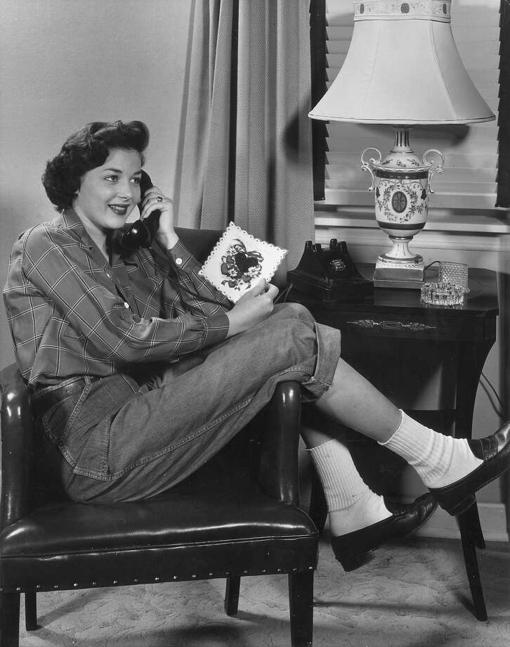 1955:  A teenage girl wearing loafers and blue jeans rolled up the knee sits on a leather chair talking on a telephone. She holds a Valentine's card in her hand and is smiling. Photo: Lambert, Getty Images / Archive Photos