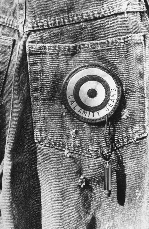 Back pocket of a pair of bullet-hole riddled Calamity Jeans, including their logo, a leather bullseye with an actual bullet dangling off it from a leather strip in 1987. Photo: Evelyn Floret, Time & Life Pictures/Getty Image / Evelyn Floret