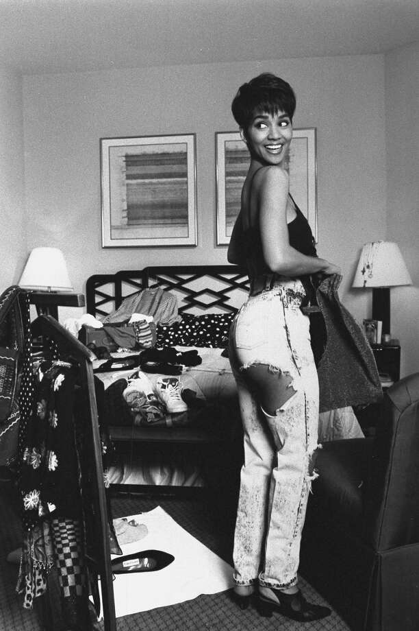 Actress Halle Berry in black brassiere & ripped jeans featuring revealingly strategic holes at hip & knee, trying on outfits in cluttered bedroom of her hotel room. Photo: Mario Ruiz, Time & Life Pictures/Getty Image / Mario Ruiz