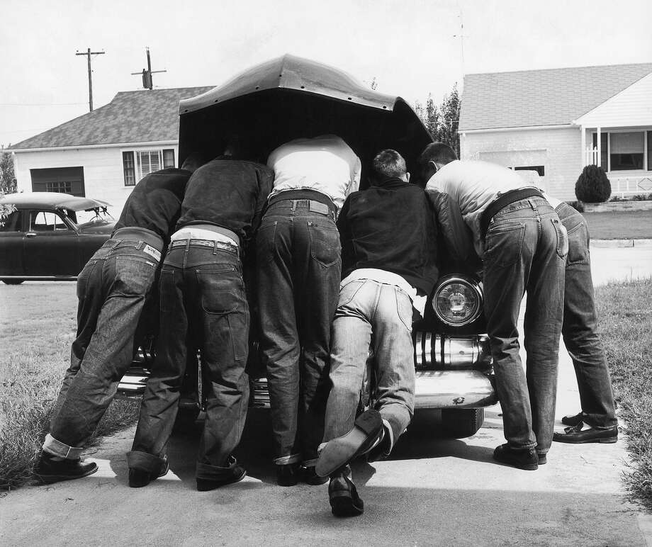 Teenager Kerry Grange with his friends, all of them wearing jeans, checking the sound of the engine on his first newly-bought used car, in 1957. Photo: A. Y. Owen, Time & Life Pictures/Getty Image / A. Y. Owen