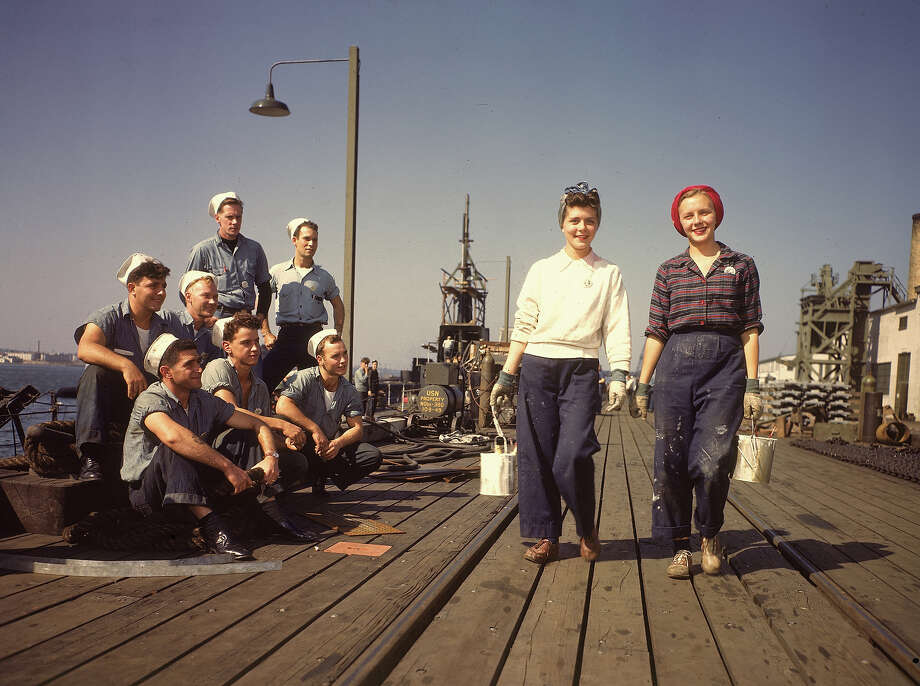 Two female war workers walk along a dock at the Electric Boat Co., cans of paint in their hands, as a group of male sailors watch them in Groton, Connecticut, October 1943. Photo: Bernard Hoffman, Time & Life Pictures/Getty Image / Time & Life Pictures