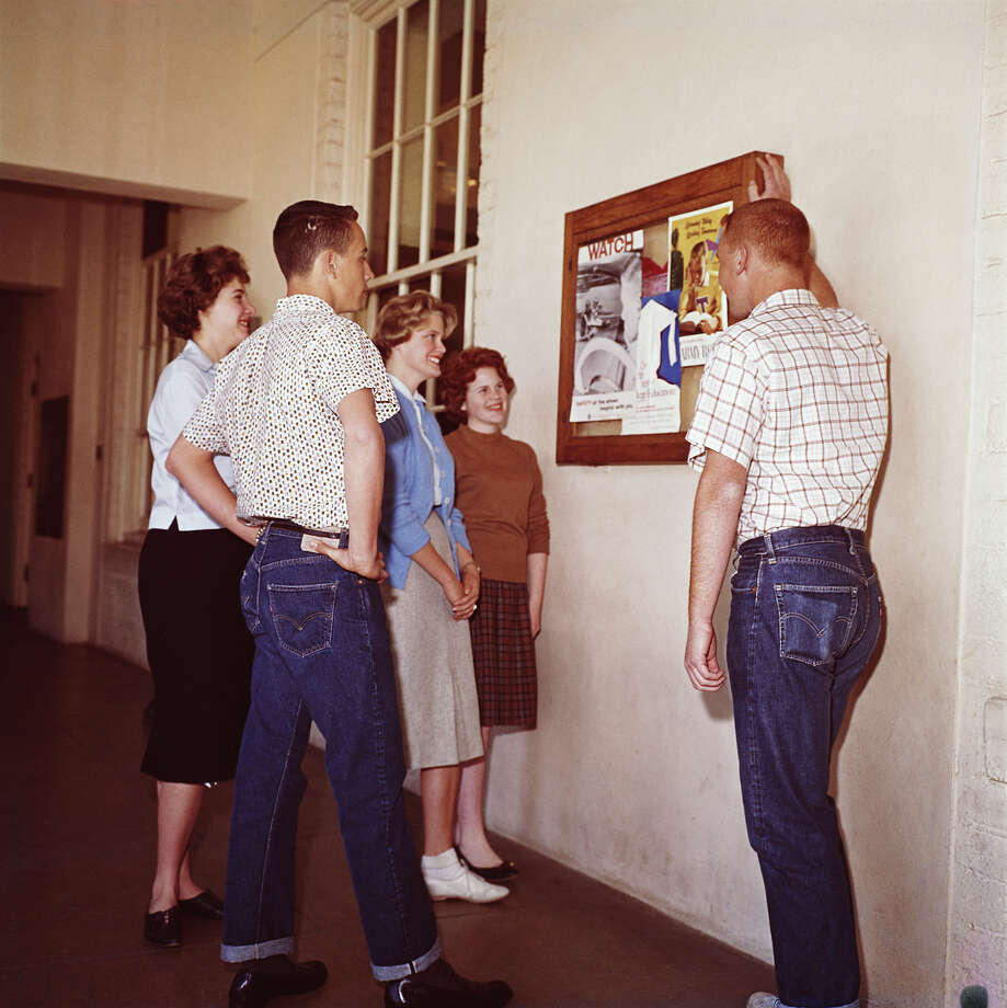 A group of college students looking at a notice board wearing dark denim, circa 1960. Photo: FPG, Getty Images / 2007 Getty Images
