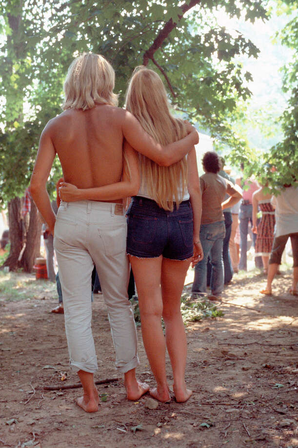 A young blonde couple viewed from behind stand at the back of the crowds at an open air event with their arms around each other cira 1970. Photo: David Redfern, Redferns / Redferns