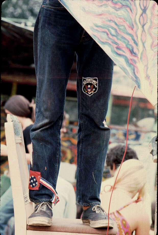 View of the legs of an unidentified person who stands on a chair to raise a kite-like flag on the 'Free Stage' at the Woodstock Music and Arts Fair, Bethel, New York, August 1969. Photo: Ralph Ackerman, Getty Images / Hulton Archive