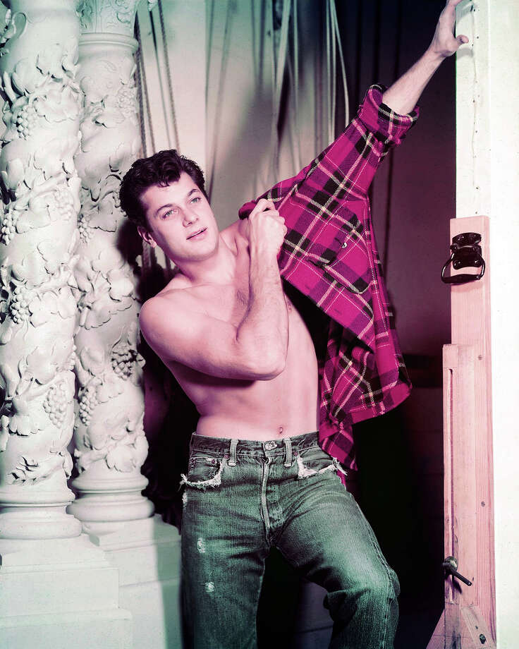 Tony Curtis (1925-2010), US actor, wearing a paid of blue denim jeans, bare-chested as he pulls on a red-and-black plaid shirt, circa 1955. Photo: Silver Screen Collection, Getty Images / 2011 Silver Screen Collection