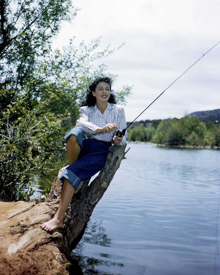 Gail Russell (1924-1961), wearing white blouse with blue stripes, and rolled up denim jeans, holding a fishing rod, circa 1955. Photo: Silver Screen Collection, Getty Images / Moviepix