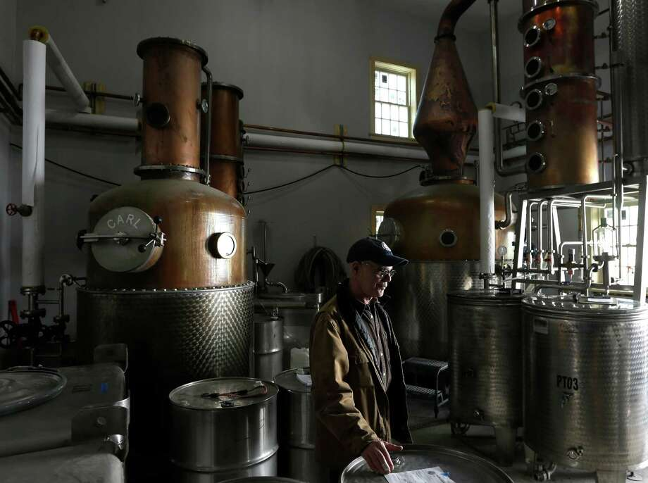 "Partner and co-founder Ralph Erenzo walks in the distillery room at Tuthilltown Spirits on Wednesday, April 17, 2013, in Gardiner, N.Y. Some call it ""grain to glass,"" the booze equivalent of the local-food slogan ""farm to table,"" though in the case of the apple vodka made from Hudson Valley at Tuthilltown, it's more like ""tree to tumbler."" Whatever the name, it's catching on. Photo: Mike Groll, AP / AP"