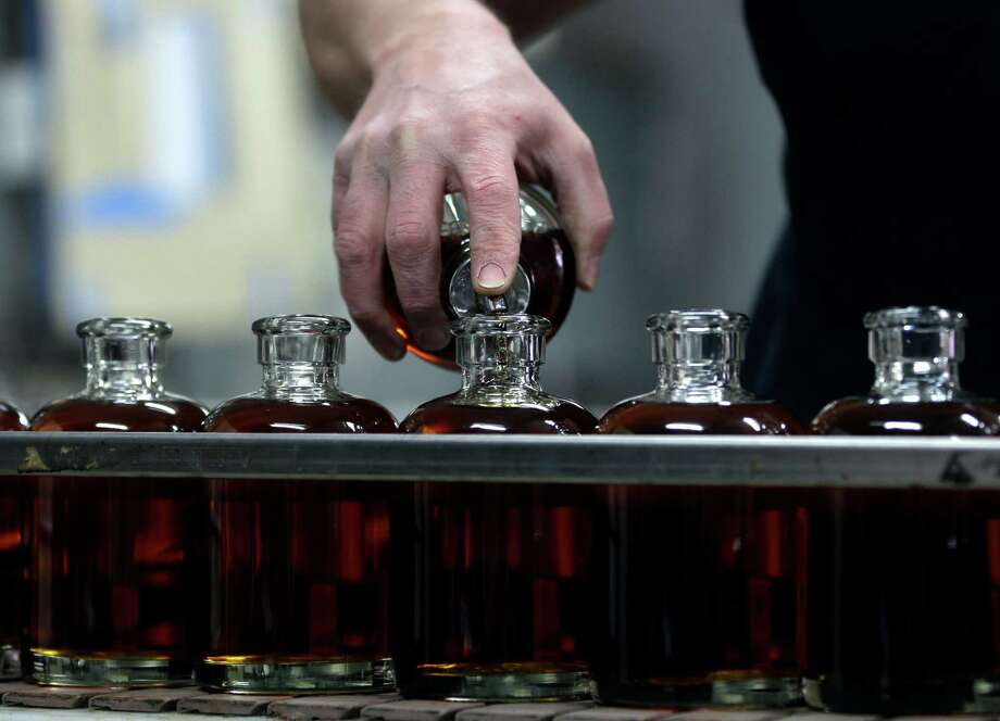 "Distilleryman Brian Messina tops off bottles of baby bourbon on the bottling line at Tuthilltown Spirits on Wednesday, April 17, 2013, in Gardiner, N.Y. Some call it ""grain to glass,"" the booze equivalent of the local-food slogan ""farm to table,"" though in the case of the apple vodka made from Hudson Valley at Tuthilltown, it's more like ""tree to tumbler."" Whatever the name, it's catching on. Photo: Mike Groll, AP / AP"