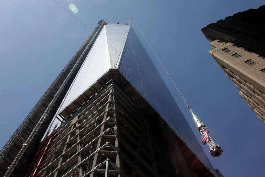 The final piece of spire, right, is hoisted to the roof of One World Trade Center, Thursday, May 2, 2013 in New York. The piece will be added to the spire at a later date, capping off the tower at 1776 feet. Photo: Mark Lennihan, AP / AP