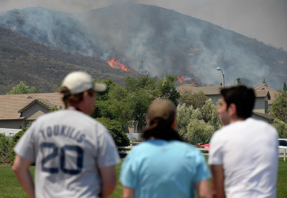 Residents watch as a wildfire approaches homes on May 2, 2013 in Newbury Park, California. Winds have made fighting the blaze, called the Springs Fire, more difficult and authorities have ordered some mandatory evacuations in the area. Photo: Kevork Djansezian, Getty Images / 2013 Getty Images