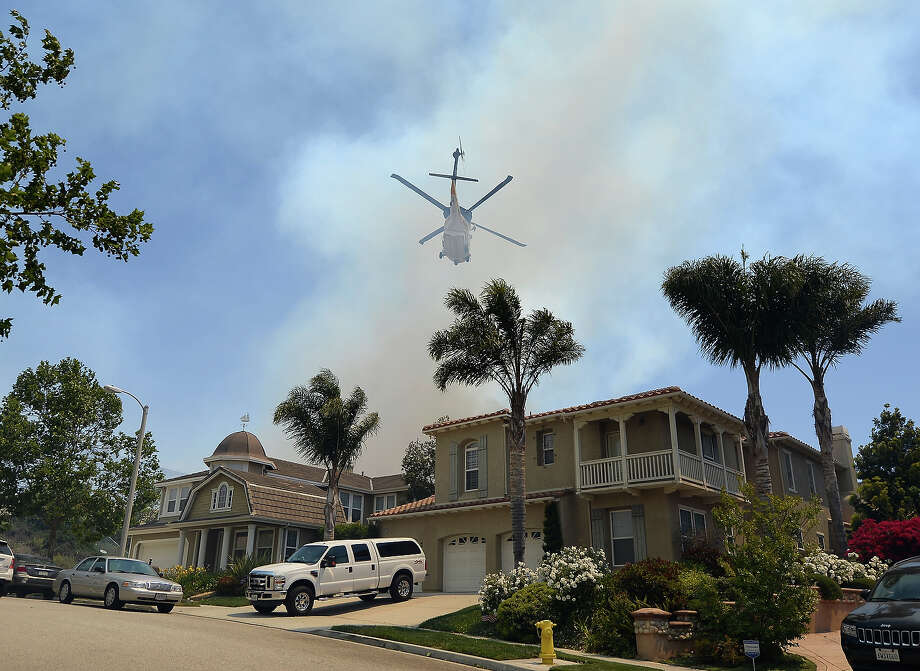 A fire fighting helicopter comes in to make a water drop behind some home threatened by a wildfire on May 2, 2013 in Newbury Park, California.  Winds have made fighting the blaze, called the Springs Fire, more difficult and authorities have ordered some mandatory evacuations in the area. Photo: Kevork Djansezian, Getty Images / 2013 Getty Images