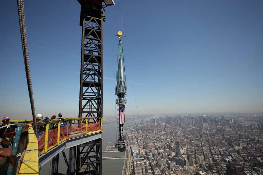 In this photo provided by the Port Authority of New York and New Jersey, one of the last two segments of the silver spire to be installed on top of One World Trade Center is hoisted to the top of the building on Thursday, May 2, 2013. With the spire as its crown, the trade center will soar to a symbolic 1,776 feet in the air, a reference to the birth of the nation in 1776. (AP Photo/Port Authority of New York and New Jersey) MANDATORY CREDIT: PORT AUTHORITY OF NEW YORK AND NEW JERSEY Photo: Uncredited, AP / Port Authority of New York and New Jersey