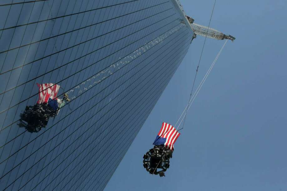 The final piece of spire is hoisted to the roof of One World Trade Center, Thursday, May 2, 2013 in New York.  The piece will be attached to the spire at a later date, capping off the tower at 1,776 feet. Photo: Mark Lennihan, AP / AP