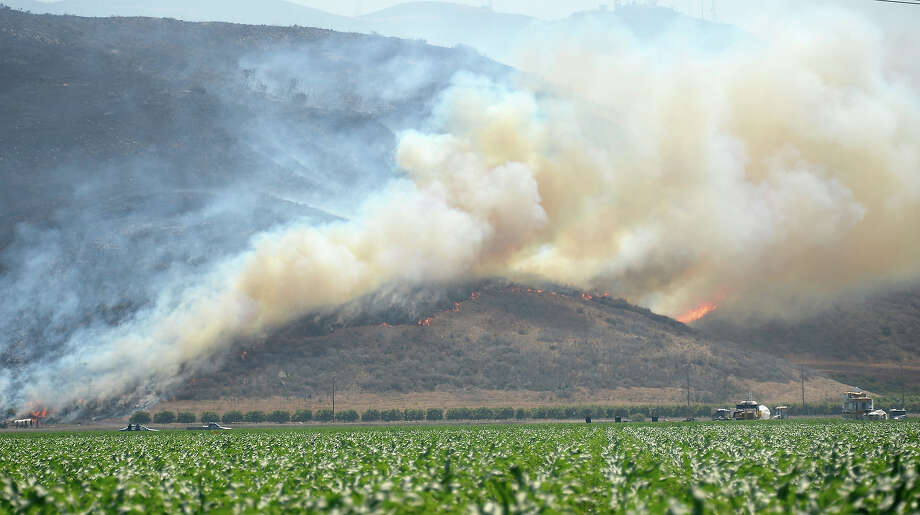 An out of control wildfire burns in the hillside near an agricultural farm on May 2, 2013 in Camarillo, California. Hundreds of firefighters are battling wind and dry conditions as over 6000 acres have already been burned northwest of Los Angeles. Photo: Kevork Djansezian, Getty Images / 2013 Getty Images