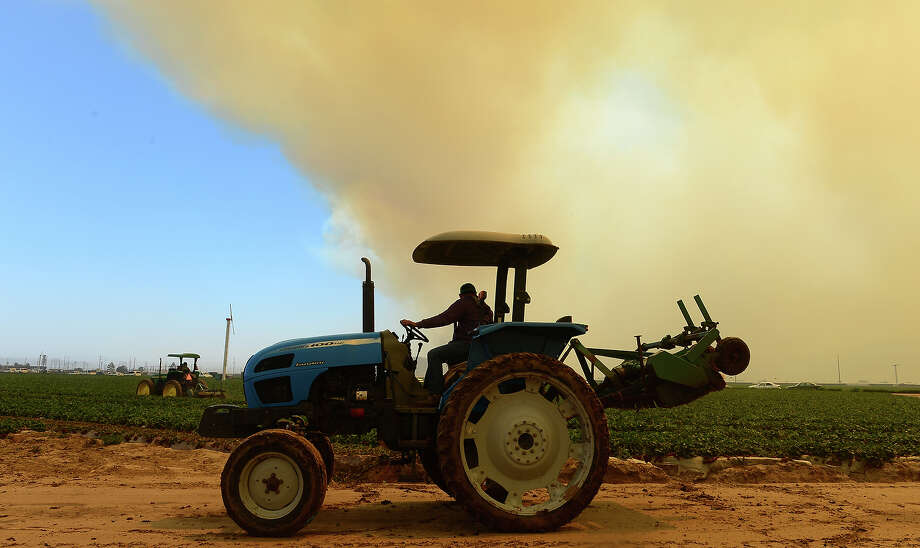 Farmers drive their tractors on farmland off the Pacific Coast Highway south of Oxnard as smoke rising into the sky and fanned by strong winds ravage hillsides and canyons in nearby Ventura County, northwest of Los Angeles on May 2, 2013. An eight-mile (13-mile) section of the Pacific Coast Highway (PCH) was closed from about 10 miles west of Malibu due the Camarillo Springs fire, the California Highway Patrol reported.  Photo: FREDERIC J. BROWN, AFP/Getty Images / 2013 AFP