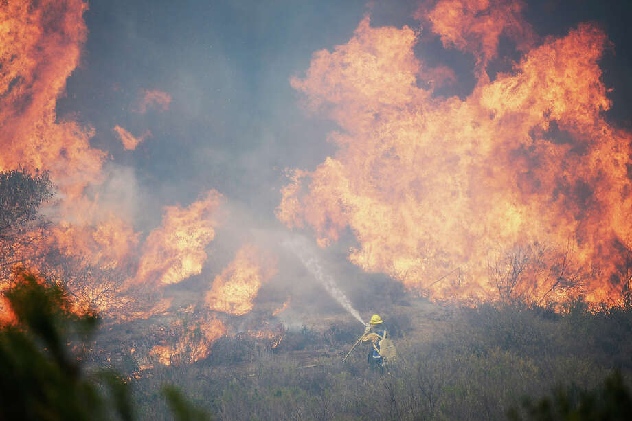 A US Forestry fire fighter fights a wall of fire during an out of control wildfire on May 2, 2013 in Camarillo, California.  Hundreds of firefighters are battling wind and dry conditions as over 6000 acres have already been burned northwest of Los Angeles. Photo: Kevork Djansezian, Getty Images / 2013 Getty Images