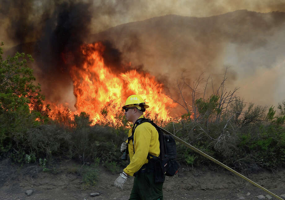 A US Forestry fire fighter preapres to take on an out of control wildfire on May 2, 2013 in Camarillo, California. Hundreds of firefighters are battling wind and dry conditions as over 6000 acres have already been burned northwest of Los Angeles. Photo: Kevork Djansezian, Getty Images / 2013 Getty Images