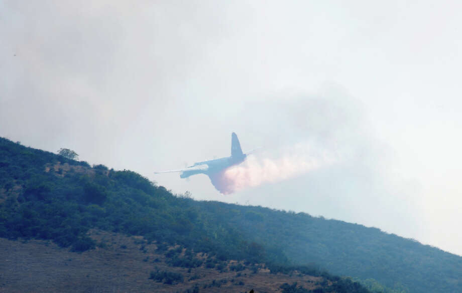 A plane drops fire retardent on an out of control wildfire on May 2, 2013 in Camarillo, California.  Hundreds of firefighters are battling wind and dry conditions as over 6000 acres have already been burned northwest of Los Angeles. Photo: Kevork Djansezian, Getty Images / 2013 Getty Images