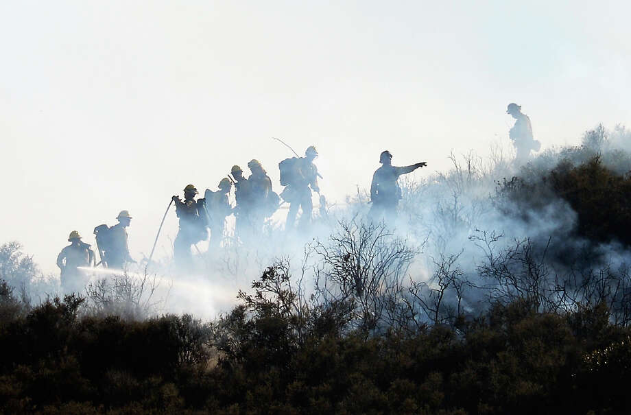 Fire firghters put out hot spots on a hillsdie behind homes by the out of control wildfire on May 2, 2013 in Newbury Park, California.  Hundreds of firefighters are battling wind and dry conditions as over 6000 acres have already been burned northwest of Los Angeles. Photo: Kevork Djansezian, Getty Images / 2013 Getty Images